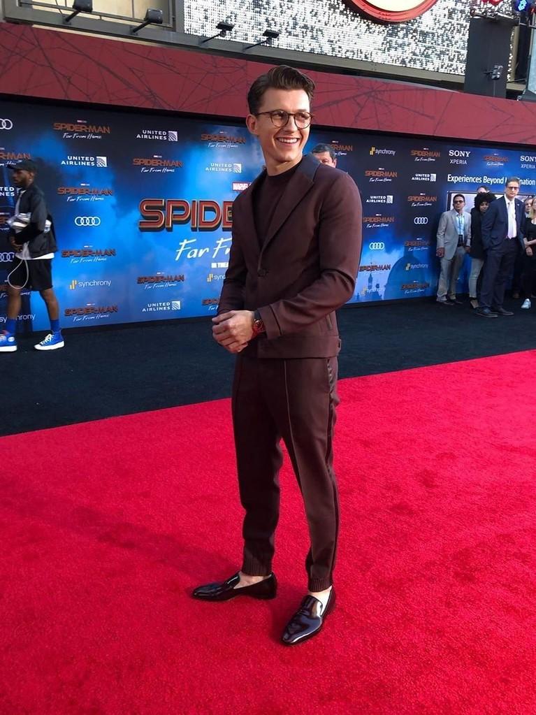 Senyuman Tom Holland saat berada di red carpet premiere film SpiderMan: Far From Home. Pemeran utama itu mengenakan setelan jas cokelat tua.