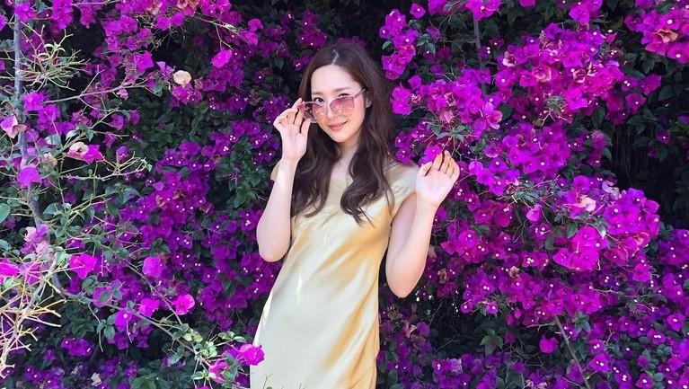 Gaya Min Young mengenakan gaun panjang berwarna emasnya. Pastinya Min Young nggak kalah cantik dari bunga ungu di belakangnya kan?