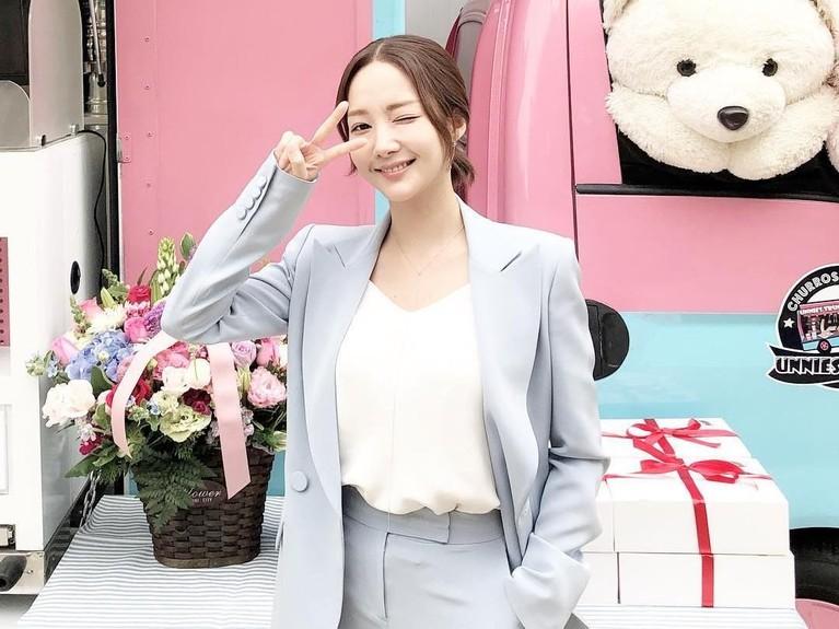 Sama dengan gaya sebelumnya, Min Young dengan setelan pakaian abu-abu muda.