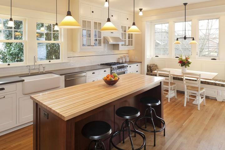 <p><em>Countertop</em> berbahan kayu pada <em>kitchen island</em> terlihat menonjol di antara dominasi warna abu-abu, metalik, dan putih. (Foto: iStock)</p>