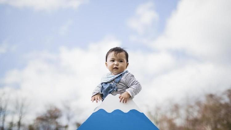 Asian baby boy climbing a miniature model of Mt.Fuji.