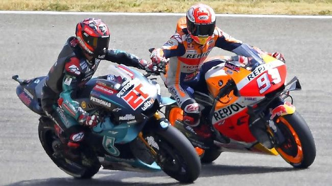 MotoGP Honda rider Marc Marquez of Spain, right, holds the hand of the 2nd placed France's rider Fabio Quartararo of the Petronas Yamaha SRT, left, after winning the MotoGP qualifying at German Motorcycle Grand Prix at the Sachsenring circuit in Hohenstein-Ernstthal, Germany, Saturday, July 6, 2019. He won the qualifying. (AP Photo/Jens Meyer)