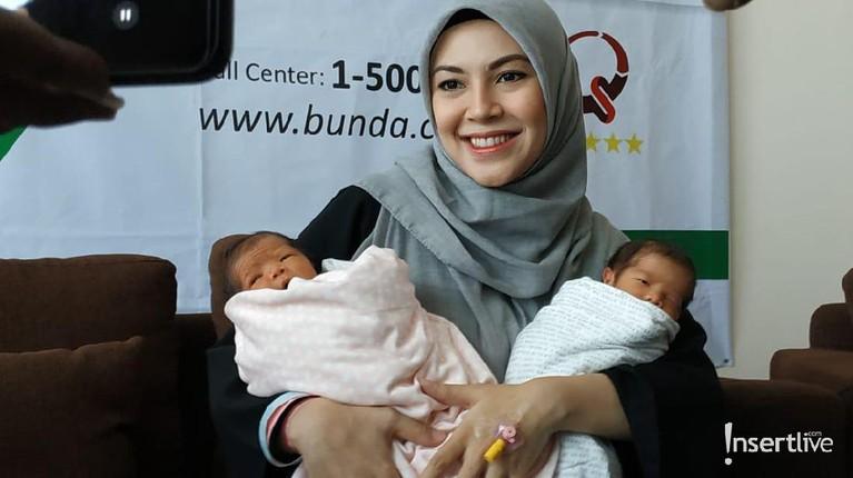 Ratna Galih menggendong bayi kembarnya saat menggelar konferensi pers terkait melahirkan anak kembarnya pada akhir pekan lalu. Ia tampak bahagia.