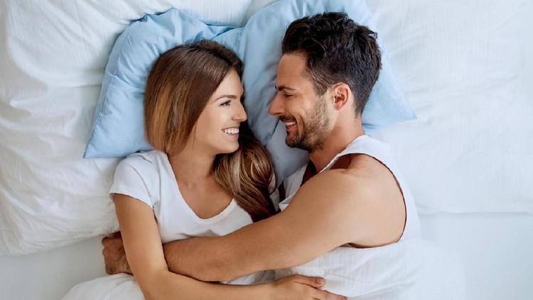 Happy young couple embracing and looking at each other while lying in bed together