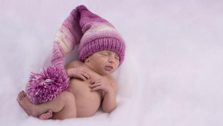 Full length of 2 weeks old newborn baby girl sleeping on stomach wearing a purple knitted hat.