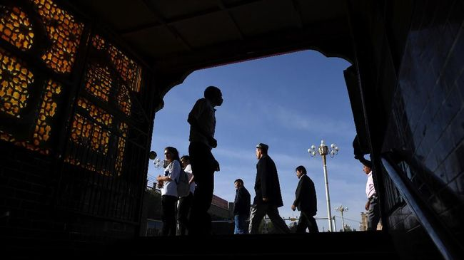 This photo taken on June 5, 2019 shows Uighur men walking past the exit of an underpass after attending Eid al-Fitr prayers, marking the end of Ramadan, in Kashgar in China's northwest Xinjiang region. - China has enforced a massive security crackdown in Xinjiang, where more than one million ethnic Uighurs and other mostly Muslim minorities are believed to be held in a network of internment camps that Beijing describes as