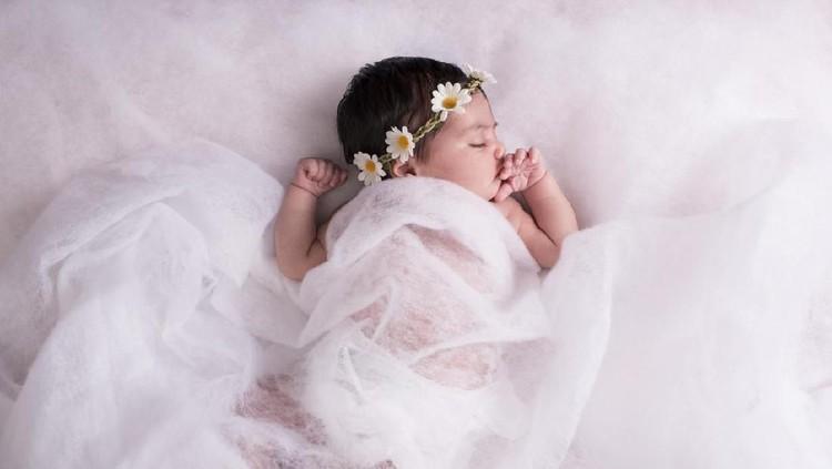2 weeks newborn baby girl sleeping on a wool fabric, wearing chamomile flower headband.