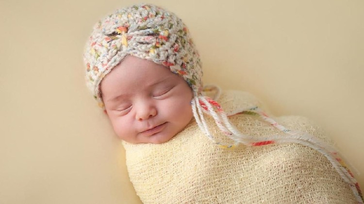 A portrait of a beautiful, two week old, newborn baby girl wearing a crocheted bonnet. She is smiling and sleeping on yellow colored fabric.