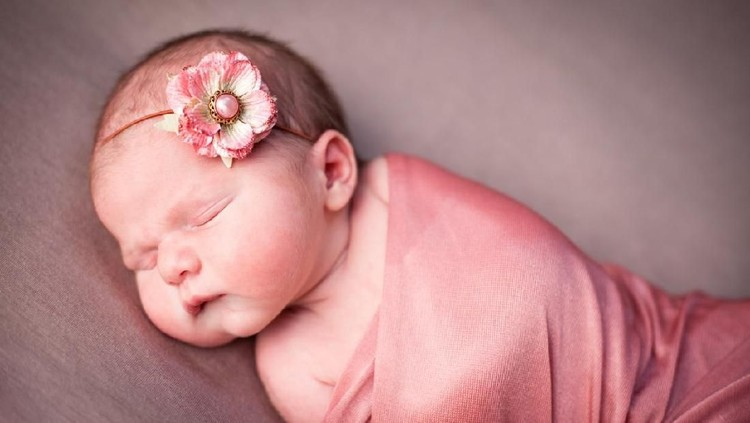 Color image of a newborn baby girl, wearing flowered headband, sleeping peacefully while wrapped in pink blanket.