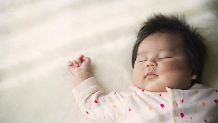Newborn baby sleeping on a white rug