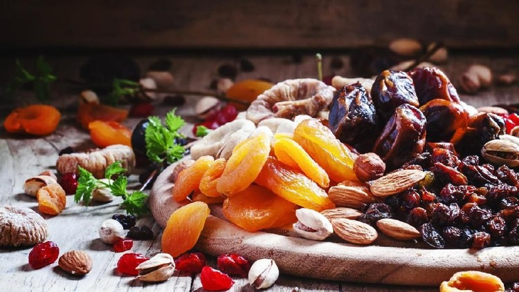 Dried apricots, dates, raisins and various nuts, vintage wooden background, selective focus