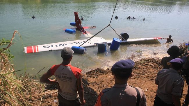 Petugas mengevakuasi pesawat latih yang jatuh di sungai Cimanuk, Indramayu, Jawa Barat, Selasa (23/7/2019). Petugas gabungan berhasil mengangkat badan pesawat Cessna 172 dengan nomor registrasi PK-WUG dari dasar sungai dan selajutnya dilakukan investigasi oleh Komite Nasional Keselamatan Transportasi (KNKT) untuk mengetahui penyebab kecelakaan tersebut. ANTARA FOTO/Dedhez Anggara/aww.