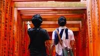 Kalau sudah romantis, tampak belakang dan bergandengan tangan pun bisa bikin baper ya, Bun. Foto ini diabadikan saat mereka jalan-jalan ke Jepang. (Foto: Instagram @prisia)