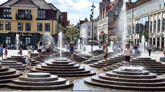 People cool down in the fountains as temperatures reached 30 degrees Celsius, at Toldbod Plads in Aalborg, Denmark, Wednesday July 24, 2019. (Henning Bagger/Ritzau Scanpix via AP)