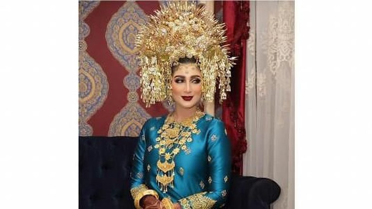 Pada malam bainai khas adat Minangkabau, Tania mengenakan dua pakaian berwarna biru dan merah lengkap dengan sunting yang berwarna emas dan ukiran henna di tangannya.