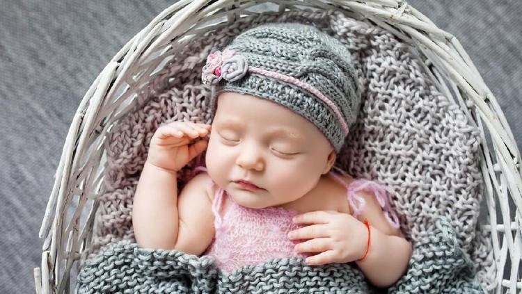Beautiful little newborn girl 1 month sleeps in a wattled basket. Clousup picture