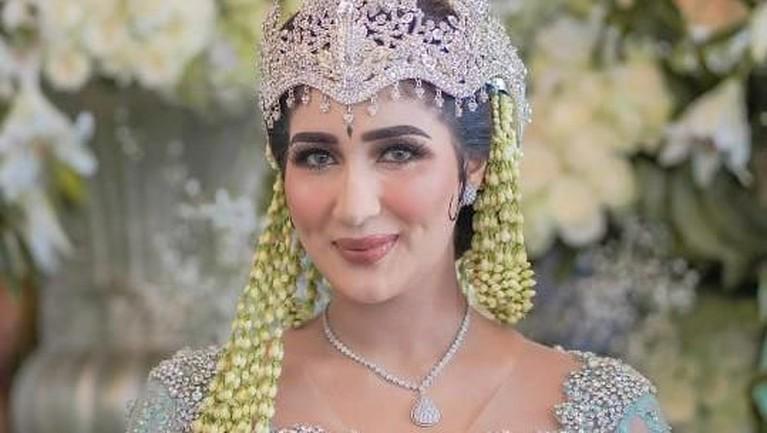 Sampai di hari akad, Tania mengenakan pakaian pengantin adat sunda berwarna biru muda lengkap dengan mahkota siger, seperti yang sudah lama didambakannya.