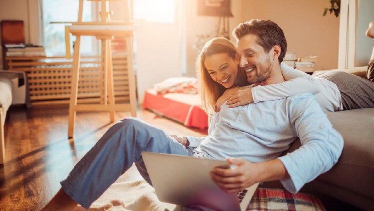 Close up of a happy young couple using laptop at home
