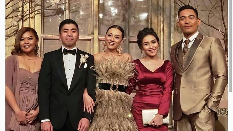 Ayu Ting Ting mengenakan gaun merwarna merah maroon ketika datang ke acara pernikahan Lolita Agustine.