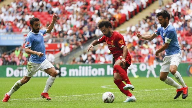 Liverpool's Mohamed Salah, centre, defends the ball from Manchester City's David Silva, right, during the Community Shield soccer match between Manchester City and Liverpool at Wembley Stadium in London, Sunday, Aug. 4, 2019. (AP Photo/Frank Augstein)