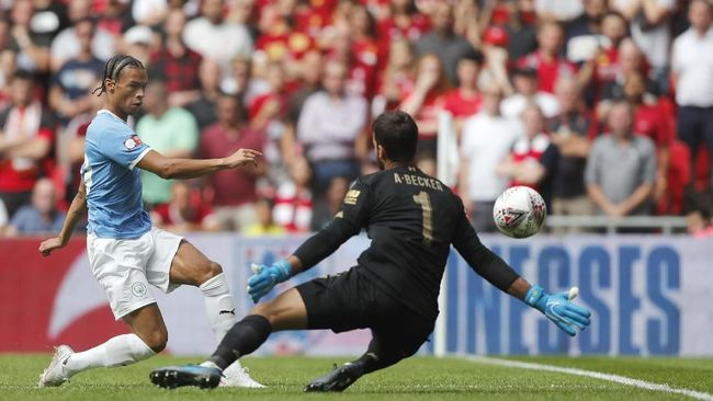 Manchester City's Leroy Sane, left, shoots at goal as Liverpool's goalkeeper Alisson Becker goes to block during the Community Shield soccer match between Manchester City and Liverpool at Wembley Stadium in London, Sunday, Aug. 4, 2019. (AP Photo/Frank Augstein)