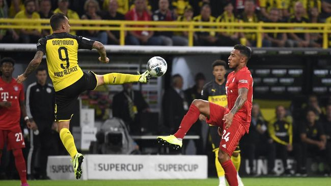 Dortmund's Spanish forward Paco Alcacer (L) and Bayern Munich's French midfielder Corentin Tolisso vie for the ball during the German Supercup foorball match BVB Borussia Dortmund v FC Bayern Munich on August 3, 2019 in Dortmund, western Germany. (Photo by INA FASSBENDER / AFP)