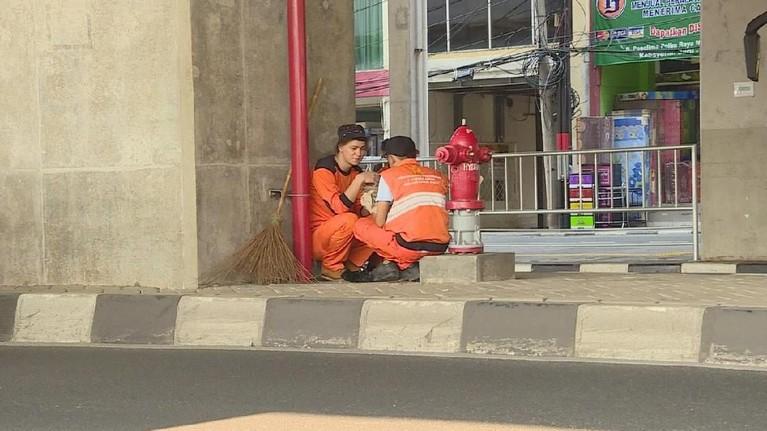 Marcell Darwin juga beristirahat sambil memakan nasi bungkus bersama salah satu personel pasukan oranye. Keduanya menikmati makan sambil berbincang hangat.