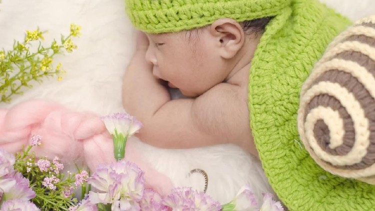 Portrait of sweet newborn baby in knitted snail costume sleeping on white blanket.selective focus shot