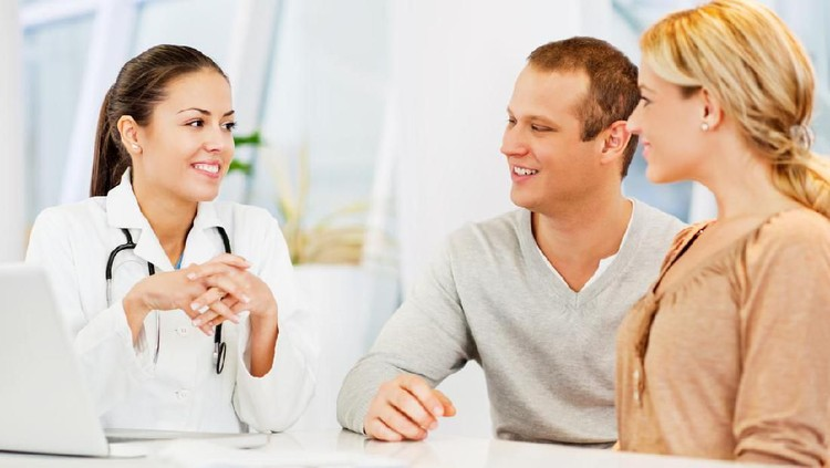 Happy Doctor Discussing With Couple In Clinic