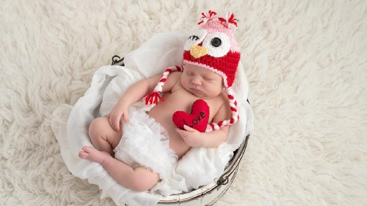 A nine day old, newborn baby girl wearing a pink and red owl hat and holding a heart shaped pillow with the word,