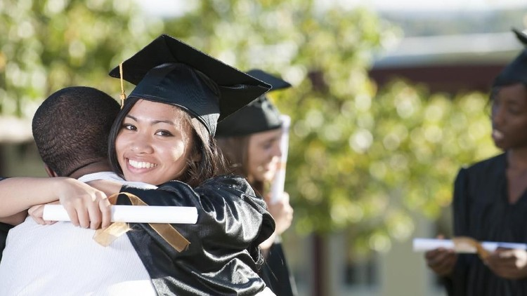 A happy graduate is hugging her friend after their graduation ceremony. She is smiling while looking at the camera.