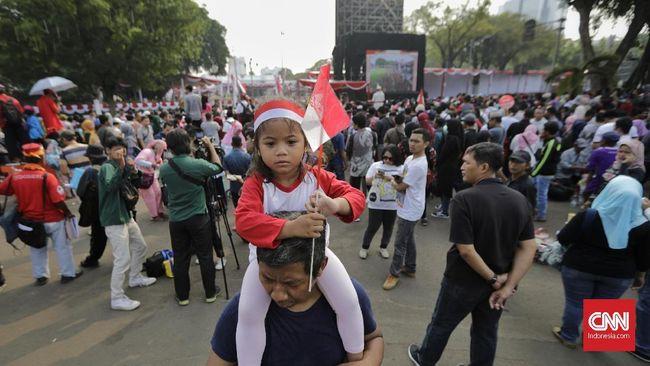 Warga menyaksikan kirab duplikat Bendera Pusaka Merah Putih dan teks Proklamasi Upacara Peringatan Detik-Detik Proklamasi di kawasan Monas, Jakarta, Sabtu, 17 Agustus 2019.