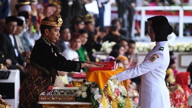 Presiden Joko Widodo menyerahkan duplikat bendera pusaka kepada Paskibraka Tarrisa Maharani Dewi saat  Upacara Peringatan Detik-Detik Proklamasi Kemerdekaan Indonesia ke-74 Tahun 2019 di Istana Merdeka, Jakarta, Sabtu (17/8/2019). ANTARA FOTO/Wahyu Putro A/foc.