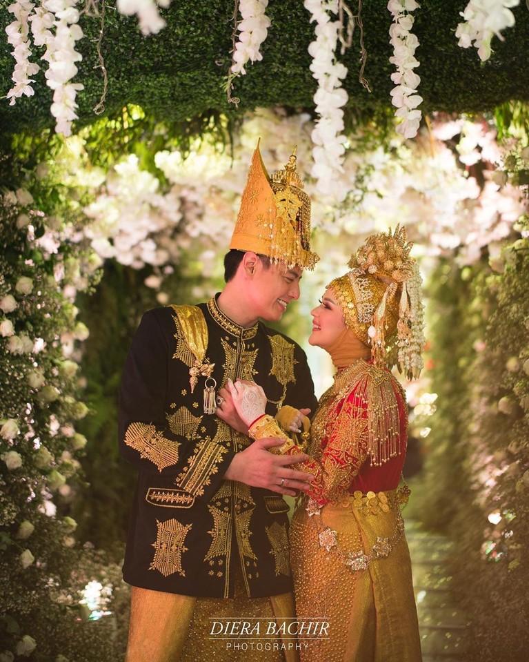 Keduanya nampak serasi mengenakan pakaian baro, adat Aceh ini.