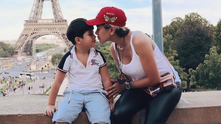 Momen Nikita Mirzani dengan Azka saat berlibur ke Paris, Prancis. Nikita dan Azka berpose dengan latar belakang menara Eiffel.