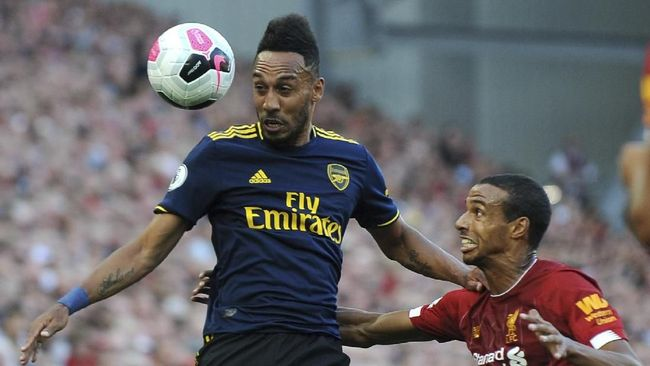 Liverpool's Joel Matip, right, challenges Arsenal's Pierre-Emerick Aubameyang during the English Premier League soccer match between Liverpool and Arsenal at Anfield stadium in Liverpool, England, Saturday, Aug. 24, 2019. (AP Photo/Rui Vieira)