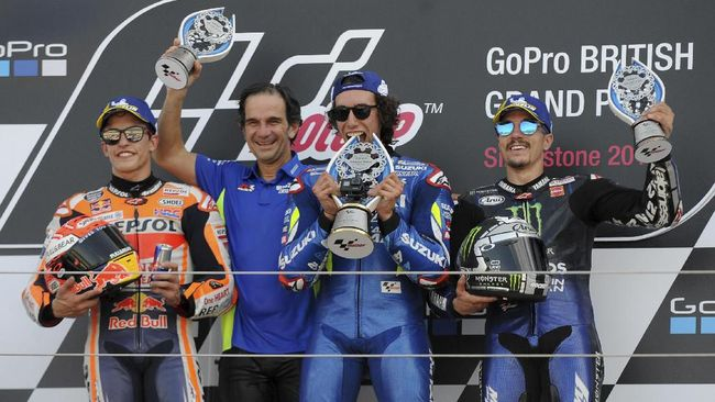 Race winner Spain's rider Alex Rins of the Team SUZUKI ECSTAR, second right, celebrates on a podium with the team principal Davide Brivio, second left, second placed Spain's rider Marc Marquez of the Repsol Honda Team, left, and third placed Spain's rider Maverick Vinales of the Monster Energy Yamaha MotoGP after the MotoGP race at the British Motorcycle Grand Prix at the Silverstone racetrack, in Silverstone, England, Sunday, Aug. 25, 2019. (AP Photo/Rui Vieira)