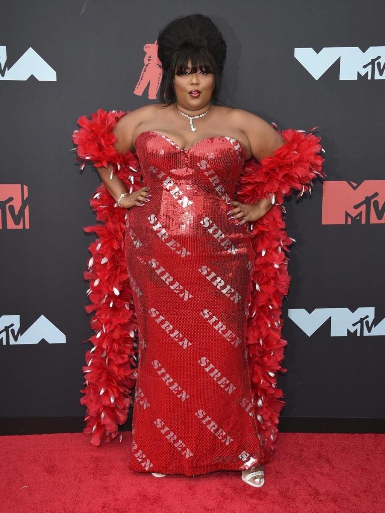 Masuk ke dalam dua nominasi, Lizzo hadir dengan mengenakan gaun merah blink-blink yang dipadukan dengan selendang bulunya.