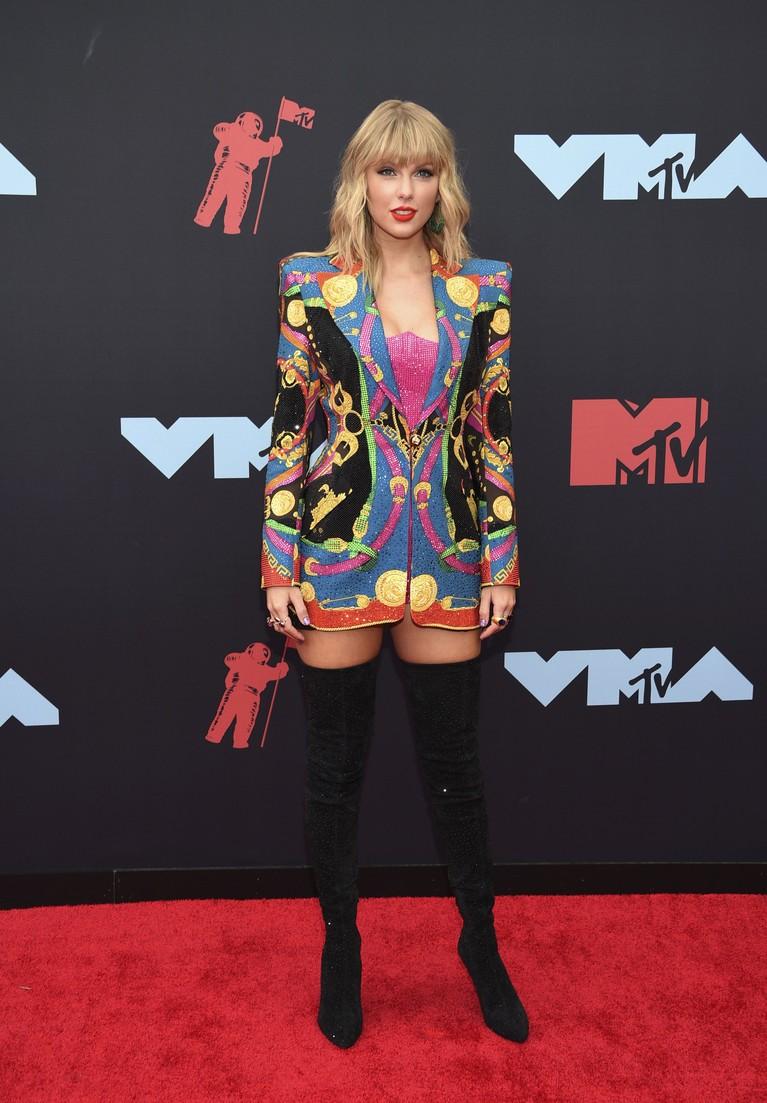 Taylor Swift juga termasuk nih ke dalam deretan seleb dengan pakaian terbaik. Ia tampil maksimal dengan blazer bermotif rancanganAtelier Versace, yang dipadukan dengan high boots hitam.