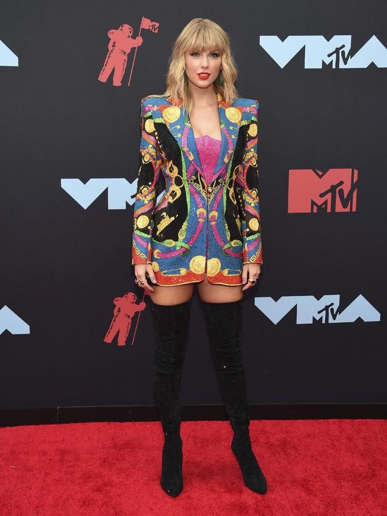 Taylor Swift memukau dengan jas warna-warninya. Ia memadukannya dengan pakaian dalaman berwarna pink kerlap-kerlip dan sepatu boots hitam tingginya.