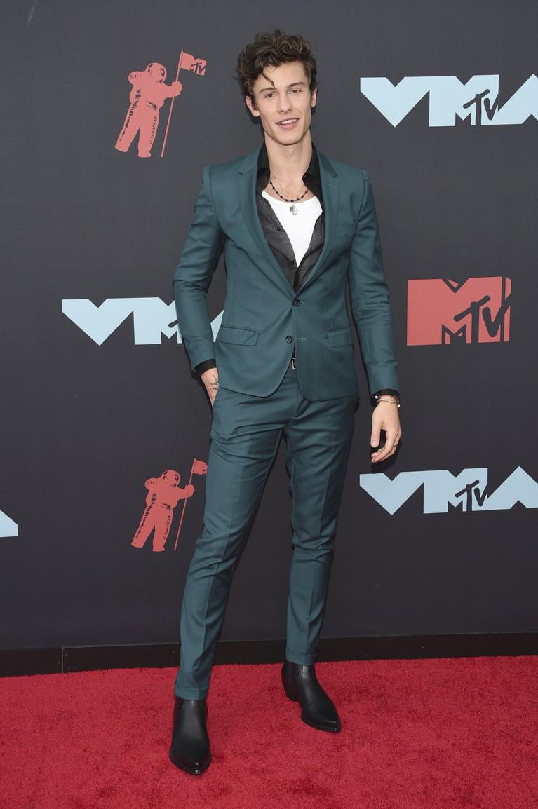 Shawn Mendes tampil kece dengan setelan jas berwarna hijau tosca yang ia padukan dengan sepatu boots hitam.