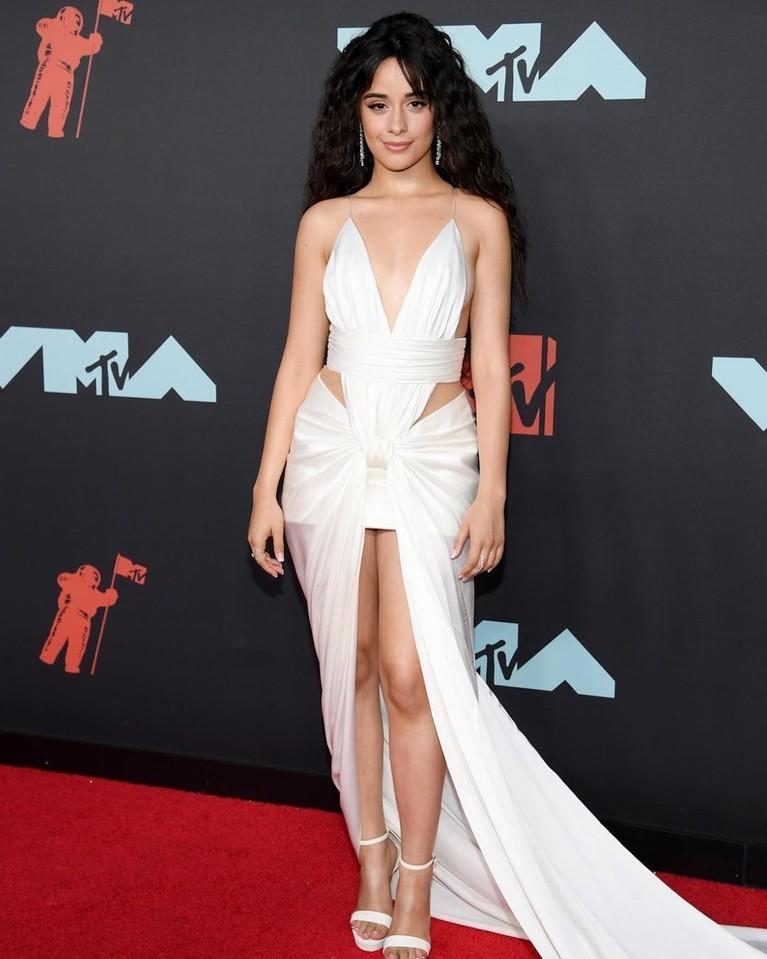 Camila Cabello tampil sempurna dengan gaun putih potongan tinggi buatan Balmain. Ia semakin memukai dengan aksesori minimalis dan gaya rambut yang dibiarkan terurai.