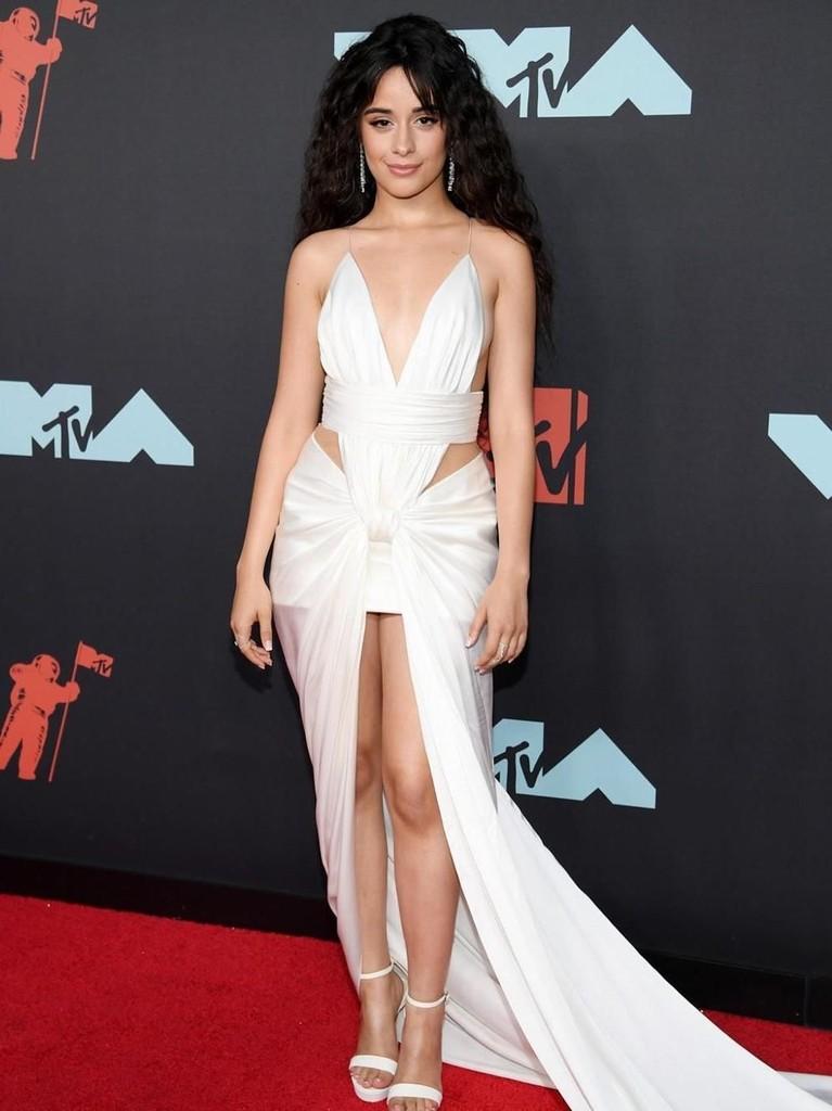 Tampil dengan riasan naturalnya, Camila Cabello terlihat cantik dengan balutan gaun putih mininya. Ia memadukannya dengan heels dan anting dengan warna yang senada.