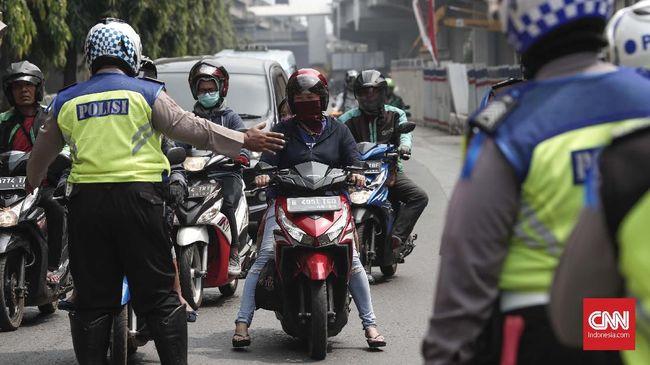 Seorang polisi lalu lintas bersikap cepat menggendong warga yang mengalami serangan jantung di sekitar Halte Transjakarta, Jakarta Barat, Jumat (14/2) pagi.