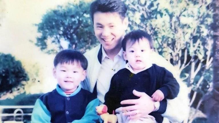 Jungkook BTS bersama kakak dan sang ayah. Jungkook yang duduk di pangkuan ayahnya dengan pipinya yang chubby.