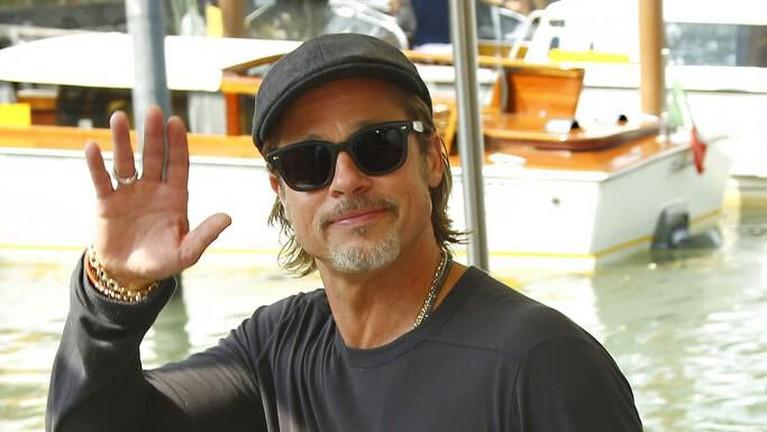 Brad Pitt tampil kasual dengan mengenakan kaos tangan panjang, kacamata dan topi. Ia melambaikan tangan ke arah fotografer dan juga penggemar.