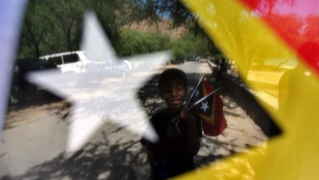 A child is seen through an East Timor's national flag as he tries to sell flags along a beach in in Dili, 12 August 2007. The World Bank says East Timor, with a population of almost one million, remains one of the world's poorest nations.  AFP PHOTO/Jewel SAMAD (Photo by JEWEL SAMAD / AFP)
