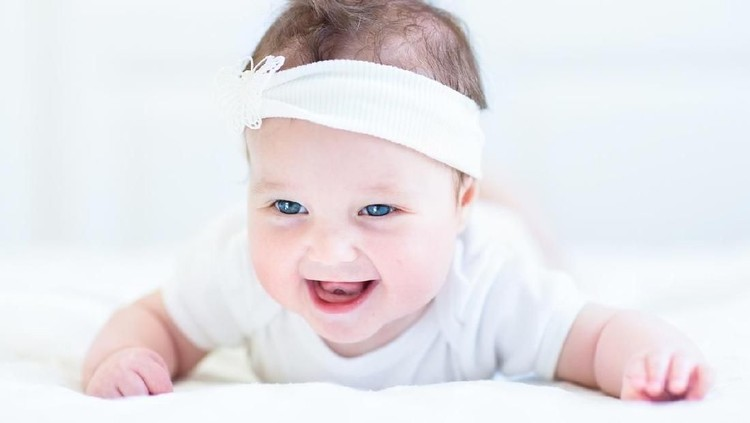 Cute laughing baby girl with a white bow playing on her tummy
