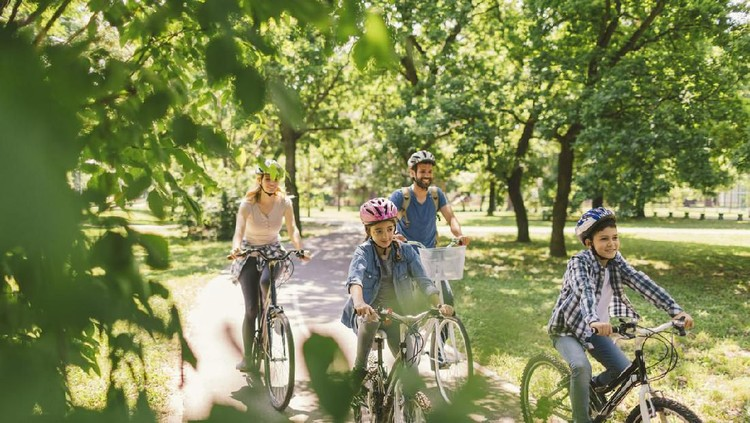 Family riding bicycle in the public park together. Cycling and enjoying the sunny day