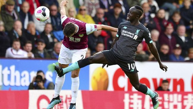 Burnley's Matthew Lowton, left, and Liverpool's Sadio Mane battle for the ball during the English Premier League soccer match at Turf Moor, Burnley, England, Saturday Aug. 31, 2019. (Anthony Devlin/PA via AP)